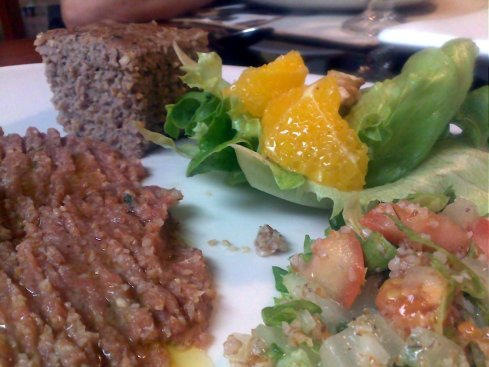 Top: kibbe bi saniyeh (kibbe in a tray) and a lettuce and orange salad with orange juice, olive oil and cinnamon dressing.  Botton: kibbe nayyeh and tabule.